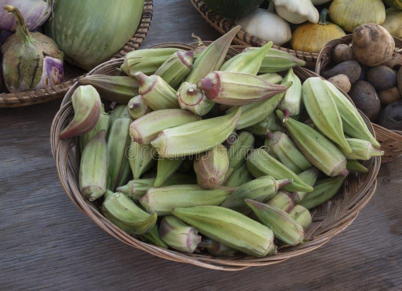 En korg mycket av okra på en bondes marknad arkivbild