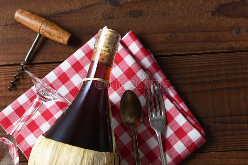 En korgflaska av Chiantivin på en röd och vit kontrollerad servett med den korkskruvgaffeln och skeden royaltyfria foton
