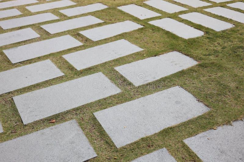 En kornväg av granit på gröngräs arkivfoto