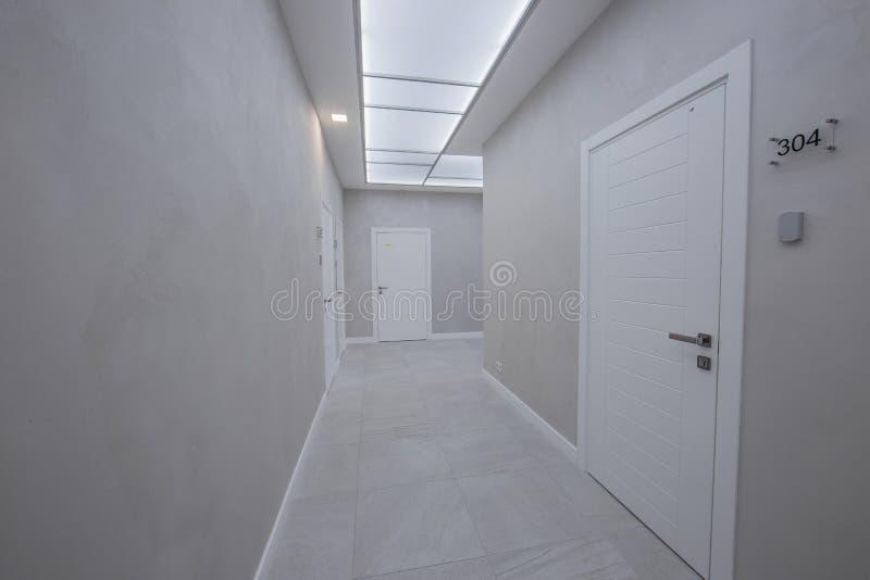En korridor i en kontorsbyggnad med ett stort antal mötesrum utan möblemang arkivbild
