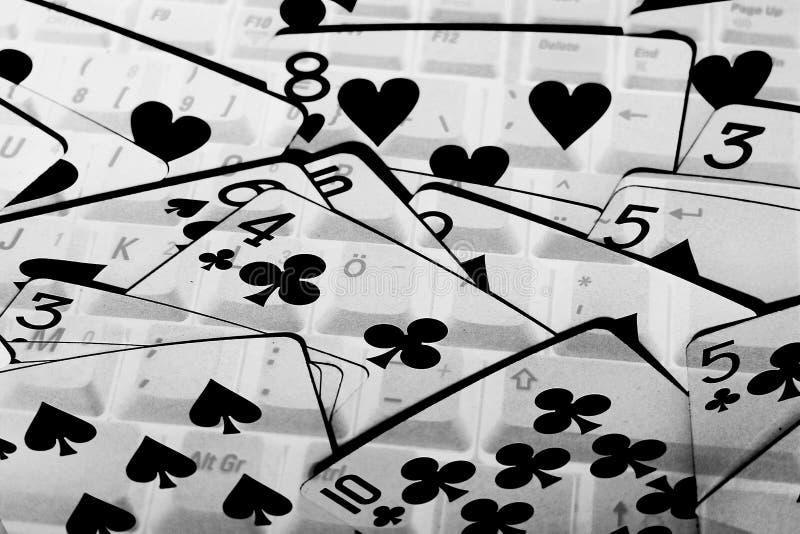 En kortlek i svartvita påfyllningar den hela bilden Ett bärbar datortangentbord ses igenom korten arkivfoton