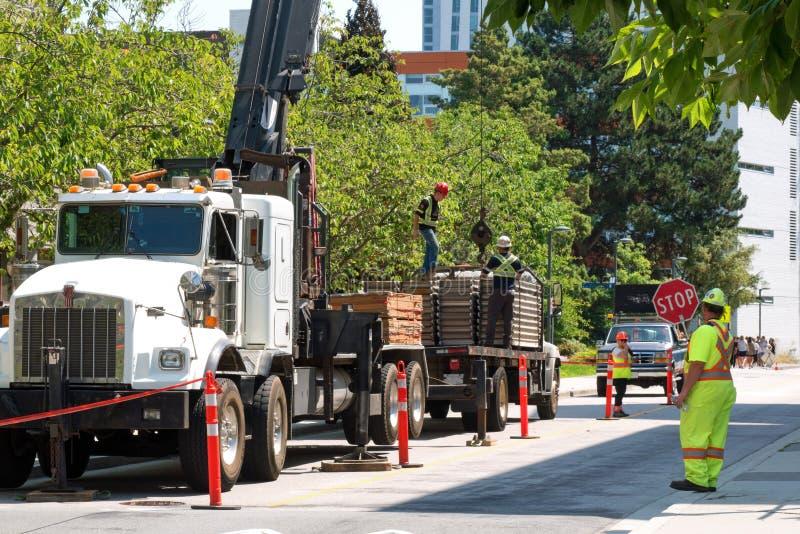 En kran och en lastbil är i handling på en stadskonstruktionsplats royaltyfri fotografi