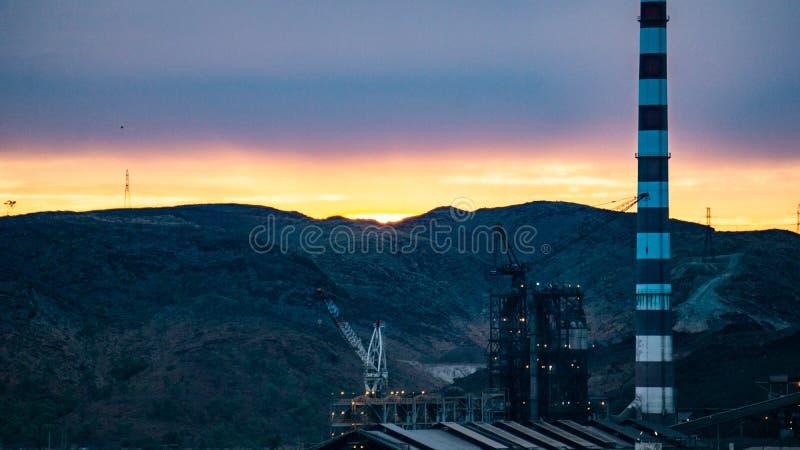 En kran och en raffinaderi som fungerar på solnedgången i monteringen Isa, Queensland arkivbilder
