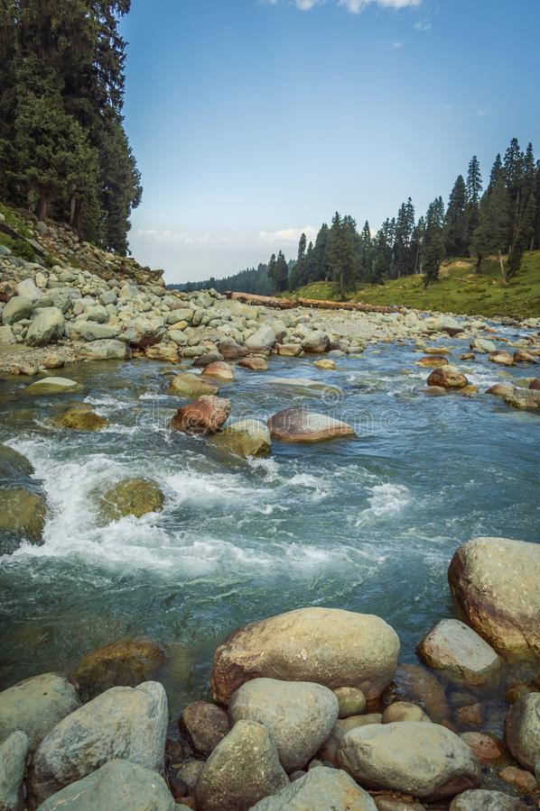 En kristallklar str?m med bl?tt vatten som fl?dar till och med en bred bergdal i Doodhpathri, Kashmir Stora stenblock i ett snabb royaltyfri fotografi