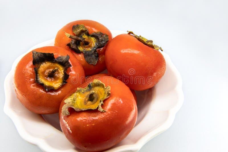 En kruka av flera röda persimoner, nytt och moget arkivbild