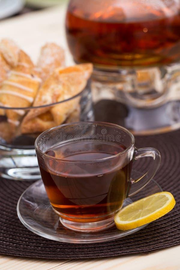 En kruka av te och kakor arkivbilder