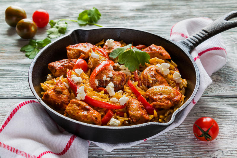 En-kruka hönafilé och orzopasta med röda spanska peppar och fetaost som lagas mat med vitlök, paprika och olivolja royaltyfria foton