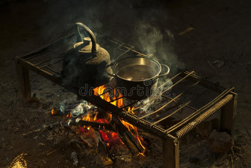 En kruka och en kokkärl på en bärbar härd som göras av metallstänger i en boning för nomad` s arkivbild