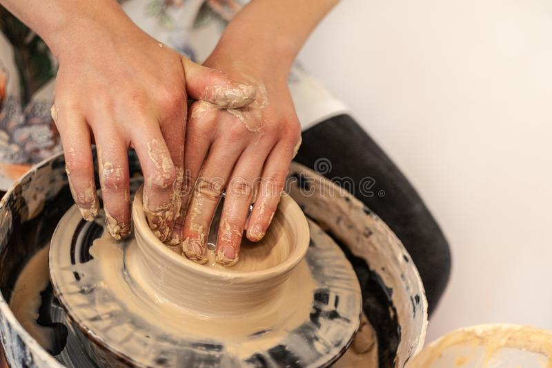 En krukmakeriprocess - ung flickas kvinnliga händer som gör lerabunken eller att råna på keramikers hjul royaltyfria bilder