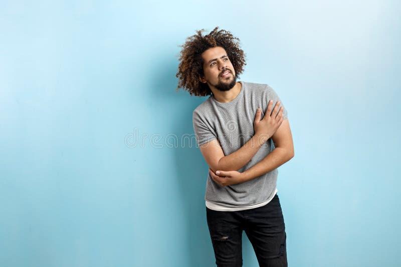 En krullhårig stilig man som bär en grå T-tröja och en riven sönder jeans, är stå och tänka med hans hand på bröstkorgen royaltyfria bilder