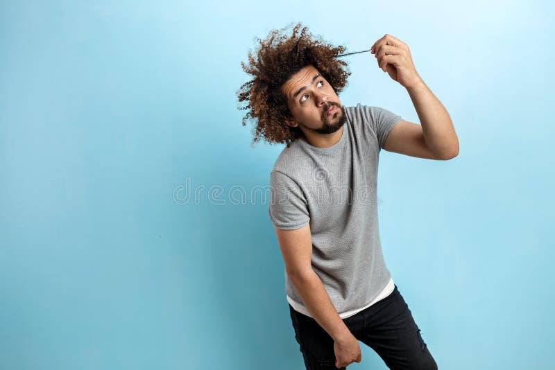 En krullhårig stilig man som bär en grå T-tröja, står med en hans fundersamt och koncentrerat blick och trycka på fotografering för bildbyråer
