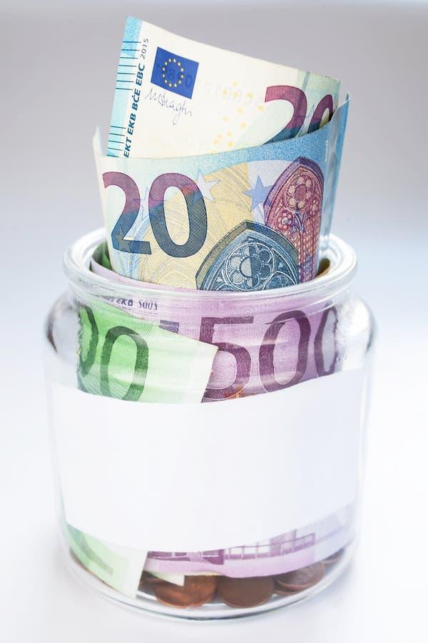 En krus med pengar arkivbild
