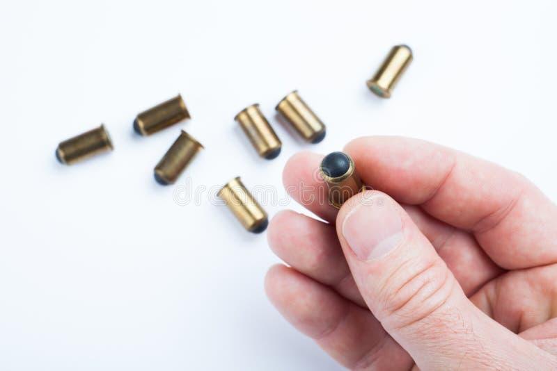 En kula för ett vapen i en mänsklig hand på en vit bakgrund _ fotografering för bildbyråer