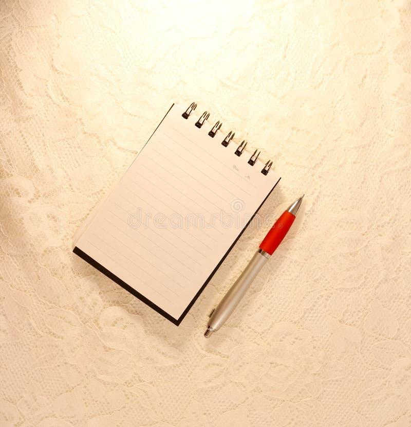 En kulspetspenna ligger bredvid en öppen anteckningsbok med den tomma sidan royaltyfri bild