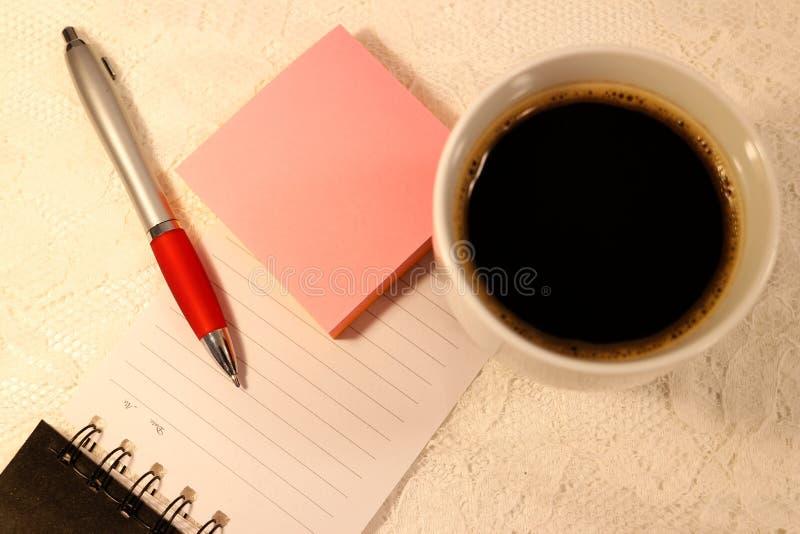 En kulspetspennabläckpenna och rosa klibbiga anmärkningslögner på en fodrad sida från en spiralanteckningsbok Och en kopp kaffe p royaltyfri fotografi