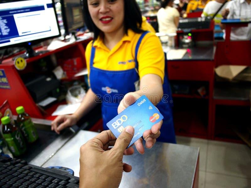 En kund använder BDO-debiteringkortet för att betala för livsmedelsbutikobjekt royaltyfri fotografi