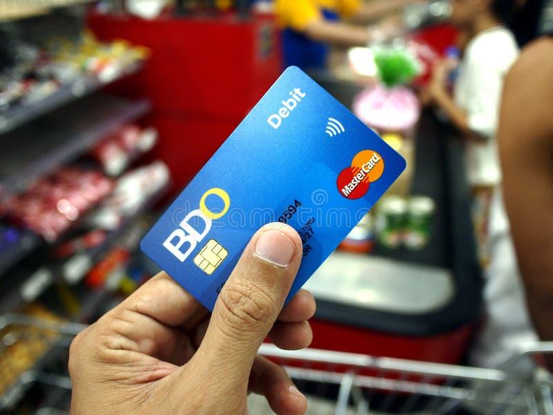 En kund använder BDO-debiteringkortet för att betala för livsmedelsbutikobjekt royaltyfria bilder
