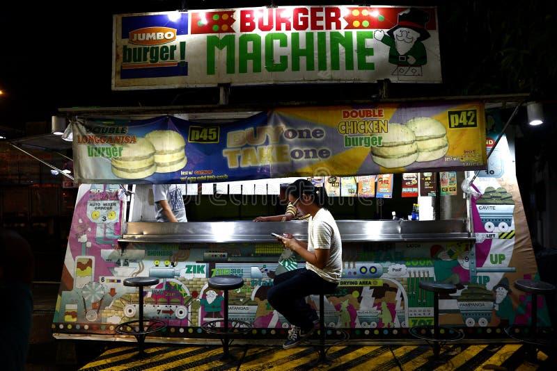En kund på en hamburgare stannar använder hans smartphone, medan vänta på hans mat royaltyfria foton