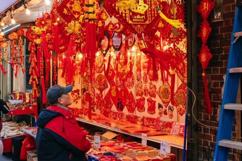En kund shoppar för kinesiska garneringar för nytt år i ett lager i kineskvarter, som det kinesiska mån- nya året, året av arkivbilder