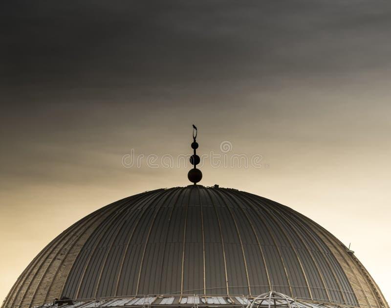 En kupolformwork av en moskékonstruktion besökte vid en fågel under mulen himmel arkivfoto