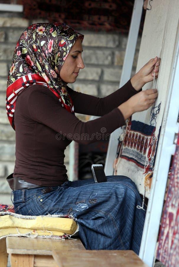 En Kurdish dam som gör en matta i skåpbil i Turkiet royaltyfria foton