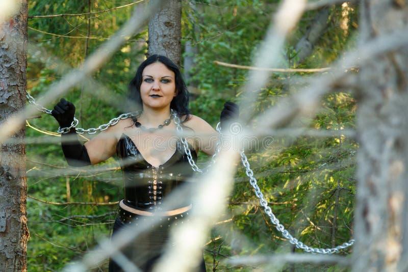 En kvinna är en häxa i svart i kedjor mellan träd i en tät skogallhelgonaafton royaltyfri fotografi