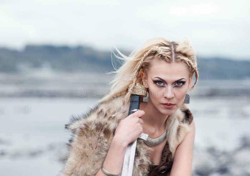 En kvinna är en krigare i en hud för varg` s med ett svärd i henne händer Flicka av vikingarna Rekonstruktion av den medeltida pl royaltyfri bild