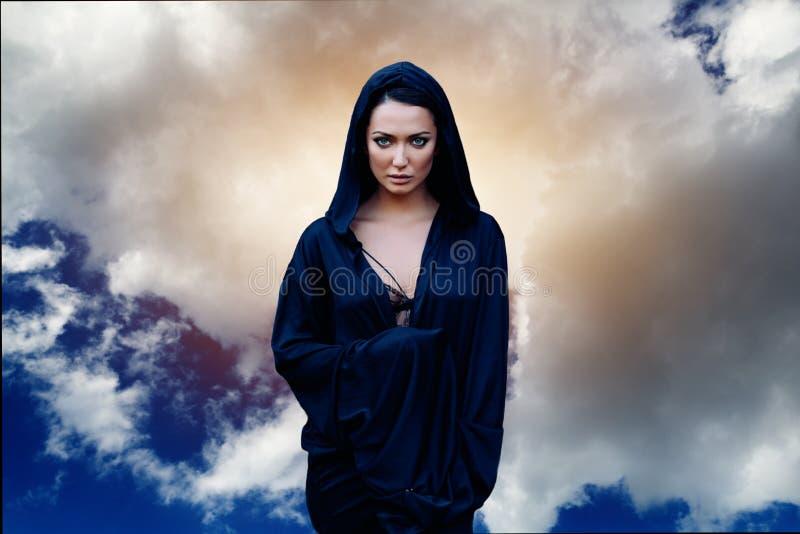 En kvinna är en profettrollkarl och en predikant i en svart mystisk kappa med en huv mot en dramatisk bakgrund royaltyfri foto