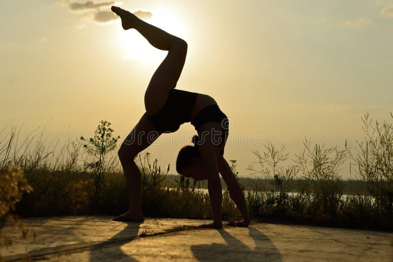 En kvinna öva yoga på en bakgrund av berg och himmel ton royaltyfria foton