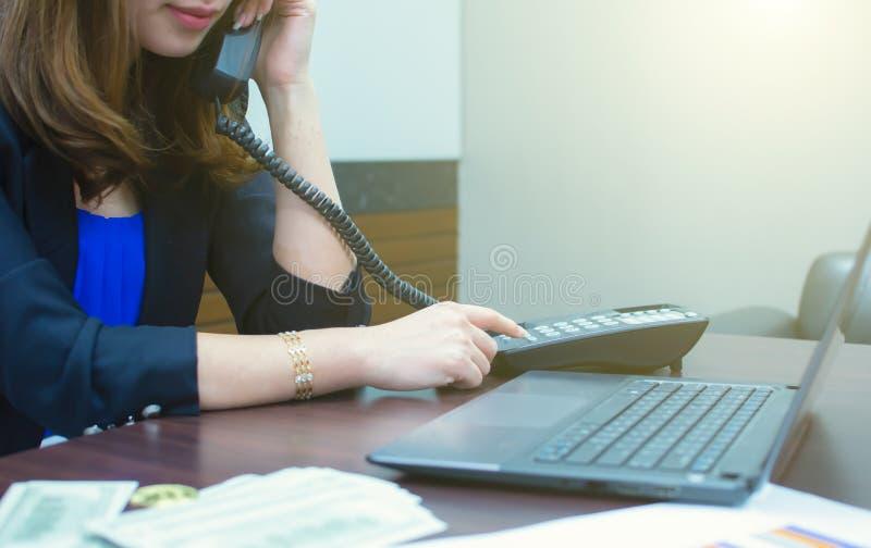 En kvinna använder telefonen och bärbara datorn för att handla hennes finansiella arbete arkivbild