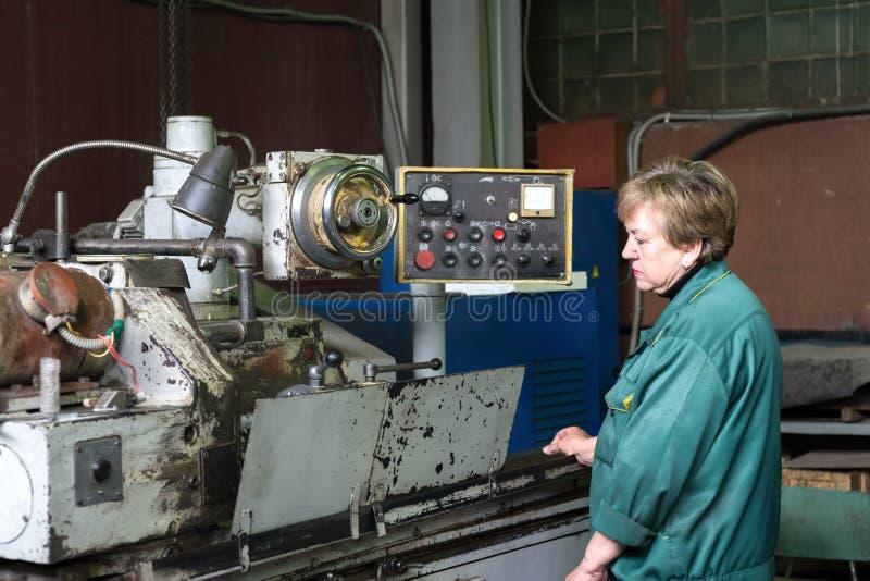 En kvinna arbetar på en inre malande maskin Etapp av metallavslutning av delar royaltyfria foton