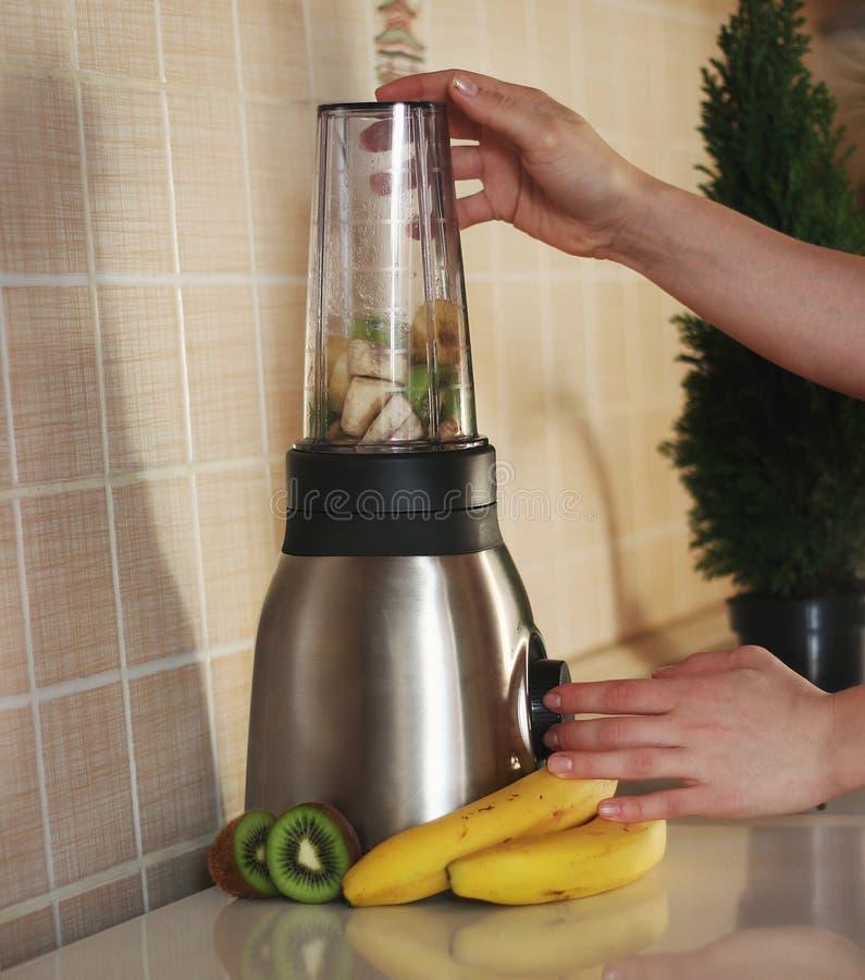 En kvinna blandar kiwin, bananer, och mandeln mjölkar för att göra en sund fruktcoctail royaltyfri bild
