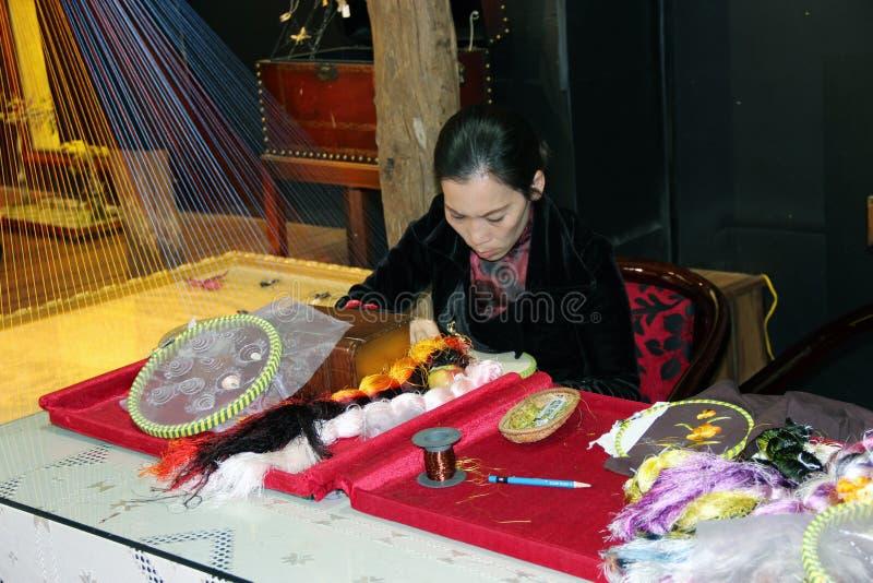 En kvinna broderar tyg royaltyfria foton