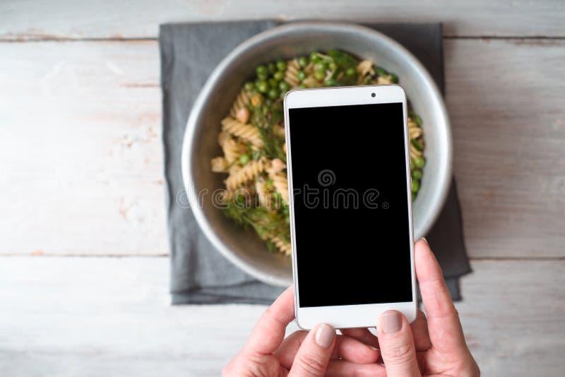 En kvinna fotograferar en lagad mat salladcloseup royaltyfria foton