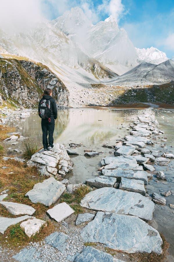En kvinna framme av en bergig sjö royaltyfria foton