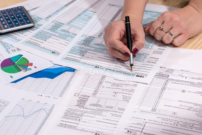 En kvinna fyller in skattformen 1040 arkivfoto