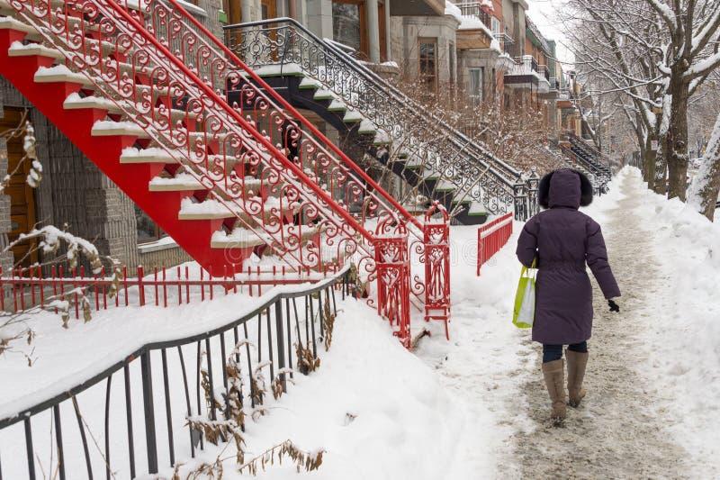 En kvinna går på en gata som täckas med snö royaltyfri bild