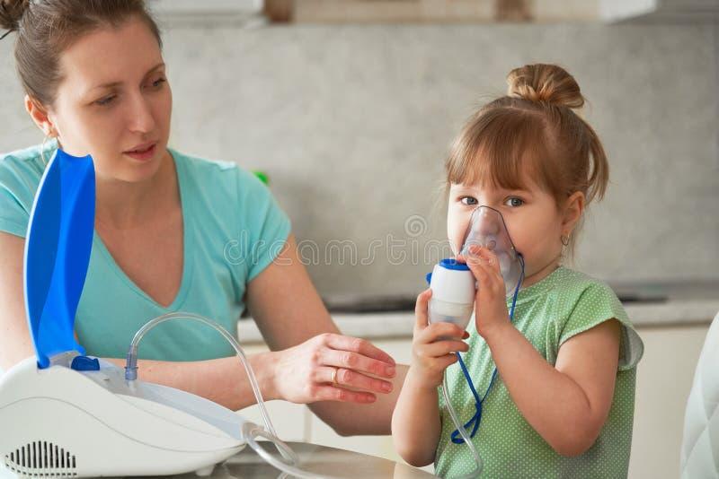 En kvinna gör inandning till ett barn hemma kommer med nebulizermaskeringen till hans framsida inhalerar dunsten av läkarbehandli arkivbild