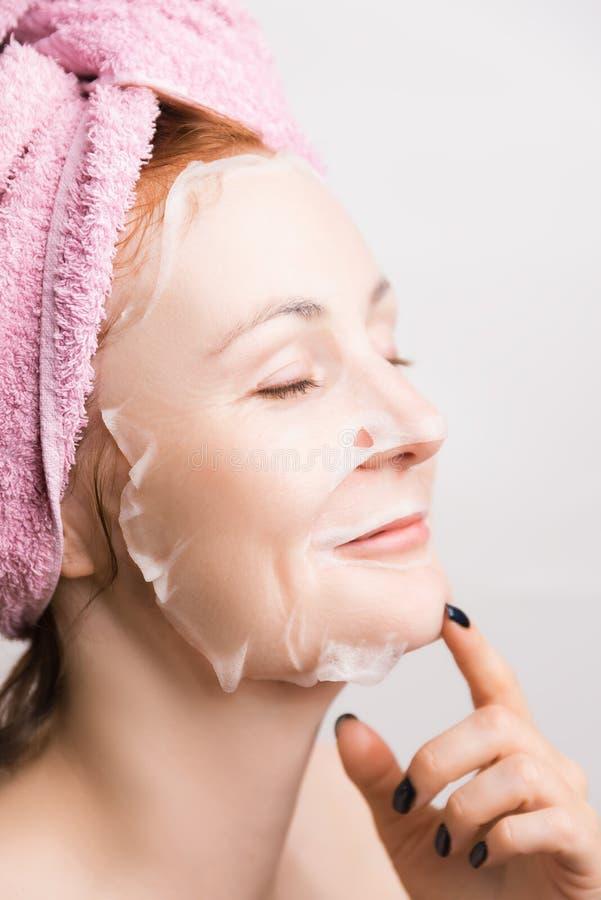 En kvinna gör en kosmetisk maskering för att fukta huden royaltyfria bilder