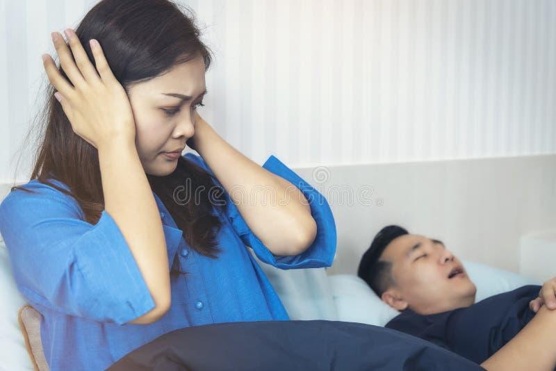 En kvinna har en otyg till mannen som han älskar att sova högt att snarka arkivfoton