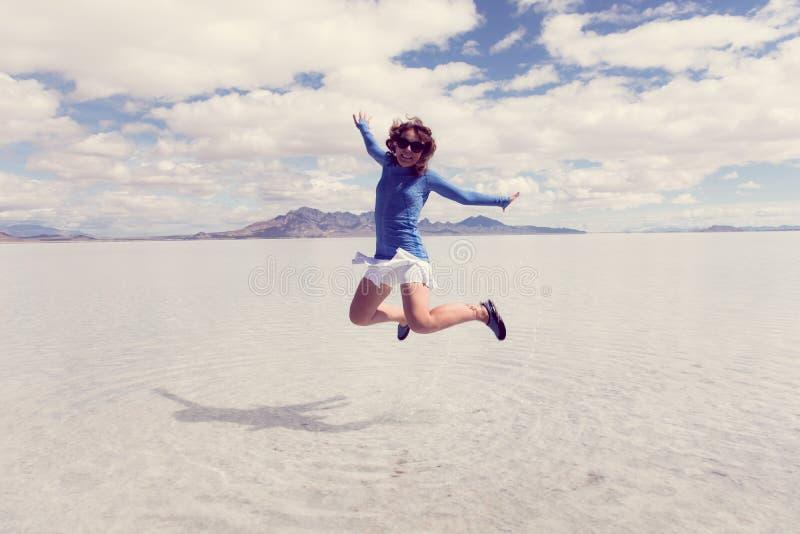 En kvinna hoppar på Bonneville de salta lägenheterna, när de salta lägenheterna översvämmas på våren arkivbilder