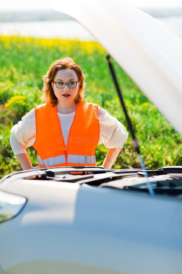En kvinna i öppen bilhätta för orange väst av den brutna bilen royaltyfri bild