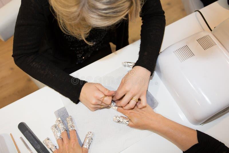 en kvinna i att spika salongen som mottar en manikyr av en blond flicka för kosmetolog arkivfoton