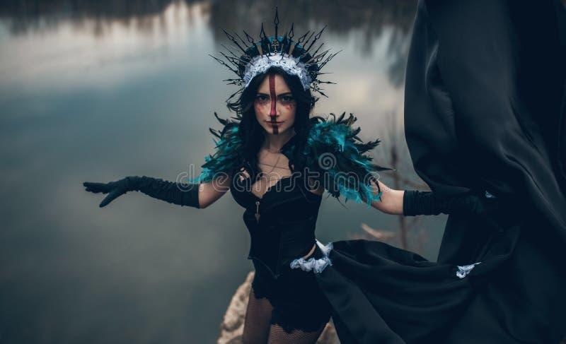 En kvinna i bilden av en fe och ett trollkvinnaanseende över en sjö i en svart klänning och en krona arkivfoton