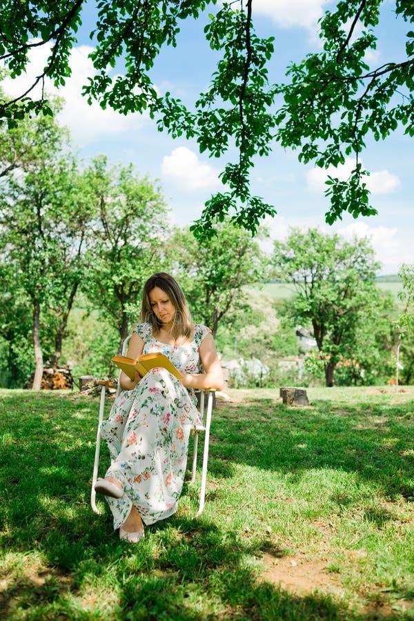 En kvinna i blommakl?nningl?sebok och sitta under tr?d royaltyfri bild