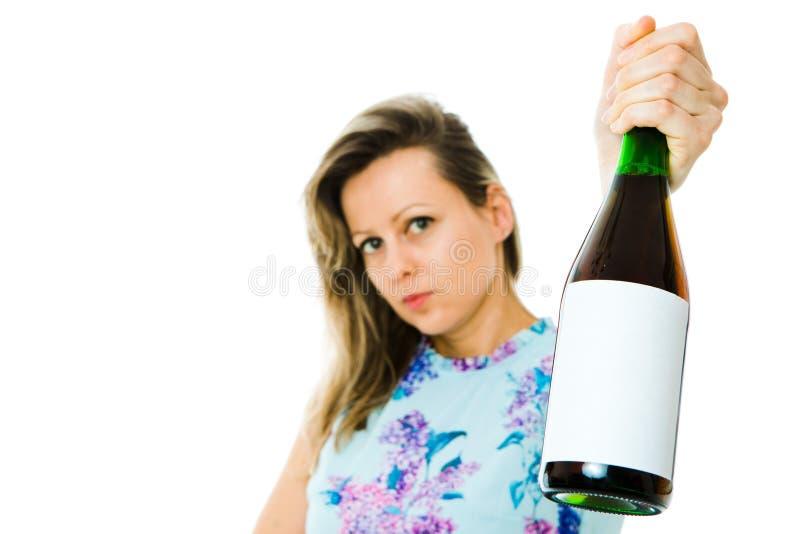 En kvinna i blommig kl?nninginnehavflaska av r?tt mousserande vin - tom etikett royaltyfri foto