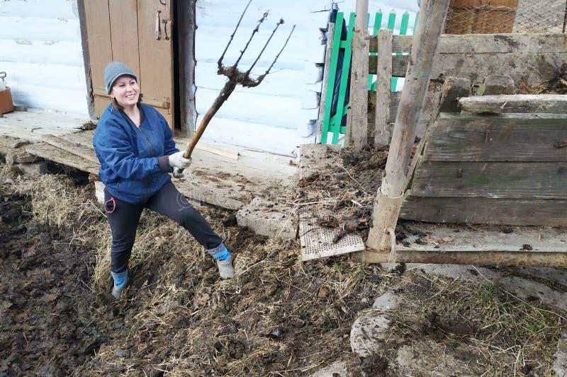 En kvinna i bygden väljer gödsel från den tidiga våren för gropen till staden arkivbilder