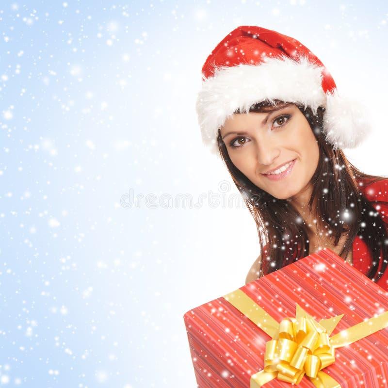 En kvinna i en julhatt som rymmer en present arkivbilder