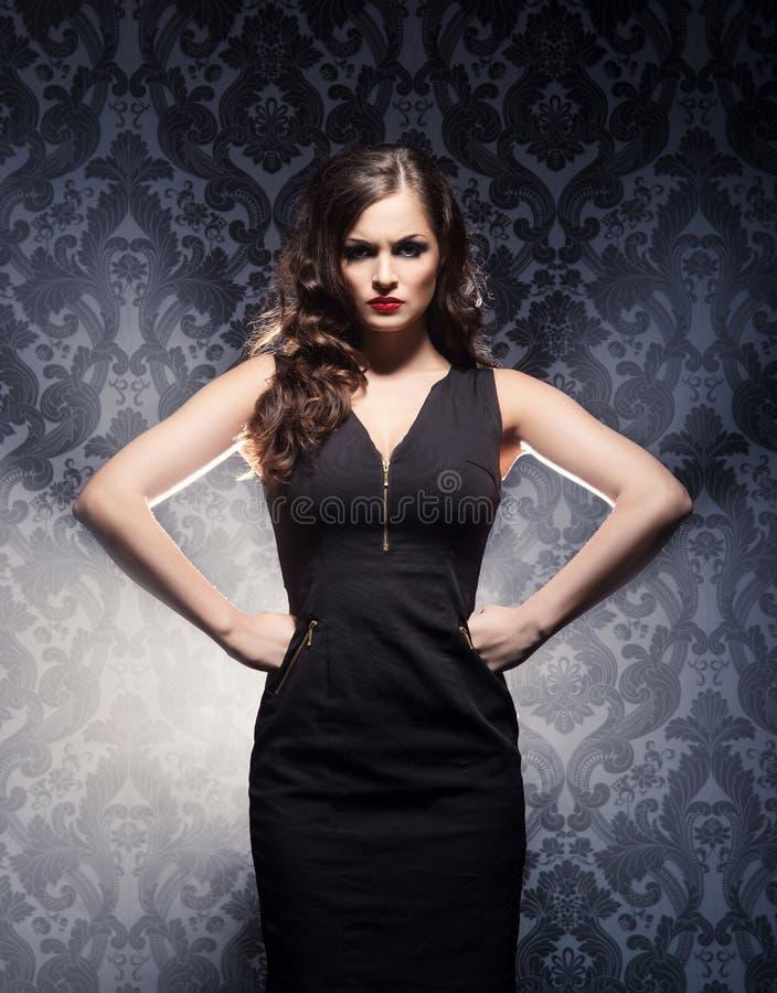 En kvinna i en modeklänning som poserar i studio fotografering för bildbyråer