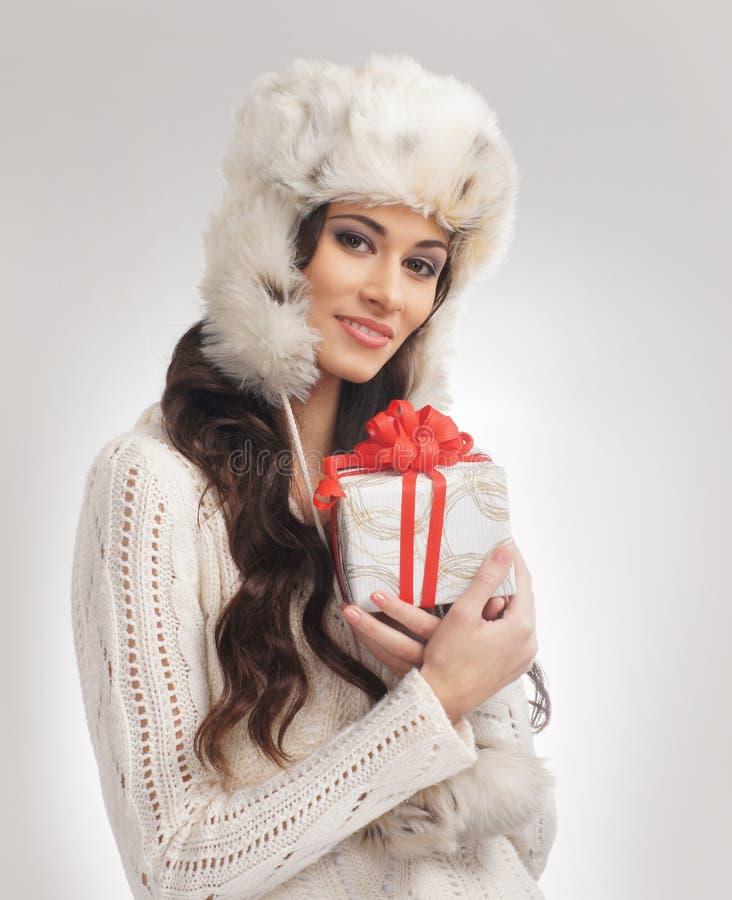 En kvinna i en varm vinterhatt som rymmer en present arkivbild